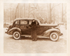 1936 Packard touring sedan and woman in fur coat on country road