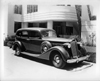 1937 Packard touring sedan in front of contemporary home