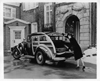 1937 Packard special station wagon, female reaching to get suitcase out of back