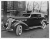1937 Packard convertible sedan, three-quarter left front view, top raised, parked by church