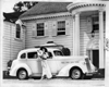 1937 Packard touring sedan with woman in long dress and hat