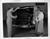 1937 Packard touring sedan, salesman showing trunk to couple