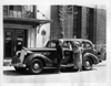 1937 Packard touring sedan in front of Packard Motor Car Co.