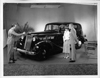 1937 Packard touring sedan, salesman speaking to couple at front side