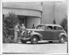 1938 Packard touring sedan parked in front of building, two men and woman by on right side of car