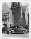 1938 Packard club coupe, left side view, parked in front of house, couple standing at door