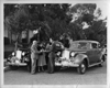 1938 Packard touring sedans parked on street, couple and salesman in between cars