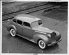 1938 Packard touring sedan parked near railroad tracks