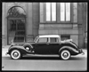 1938 Packard touring cabriolet, left side view, parked on street in front of building