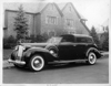 1938 Packard all weather cabriolet parked on street in front of house