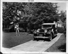 1932 Packard convertible victoria and owner Dick Powell standing on lawn near driveway