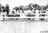 Group of men and women stand behind rail fence at a race track in Minnesota, at the 1909 Glidden Tour