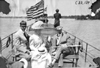 Two men and a woman sitting on bench at the bow of a boat, at 1909 Glidden Tour
