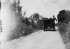 Participants passing covered-wagon in the 1909 Glidden Tour