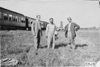 Three Glidden tourists standing near Pullman car in Kearney, Neb., at 1909 Glidden Tour