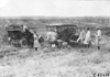 Two women look on as Glidden tourists work on their cars on the Colorado prairie, at 1909 Glidden Tour