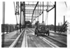 E.M.F. car crossing a large, iron bridge, on pathfinder tour for 1909 Glidden Tour