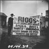 Man Holding up a Large Sign Advertising Riggs Store