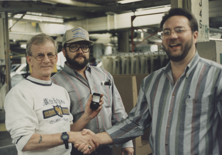 image of Subjects are, from left to right: Unknown, Rusty Zeigler (UAW Bargaining Committee), Garry Bernath (Local 602 President).  Zeigler and Bernath are presenting a UAW Local 602 ring to a union member that has achieved twenty-five years of service.