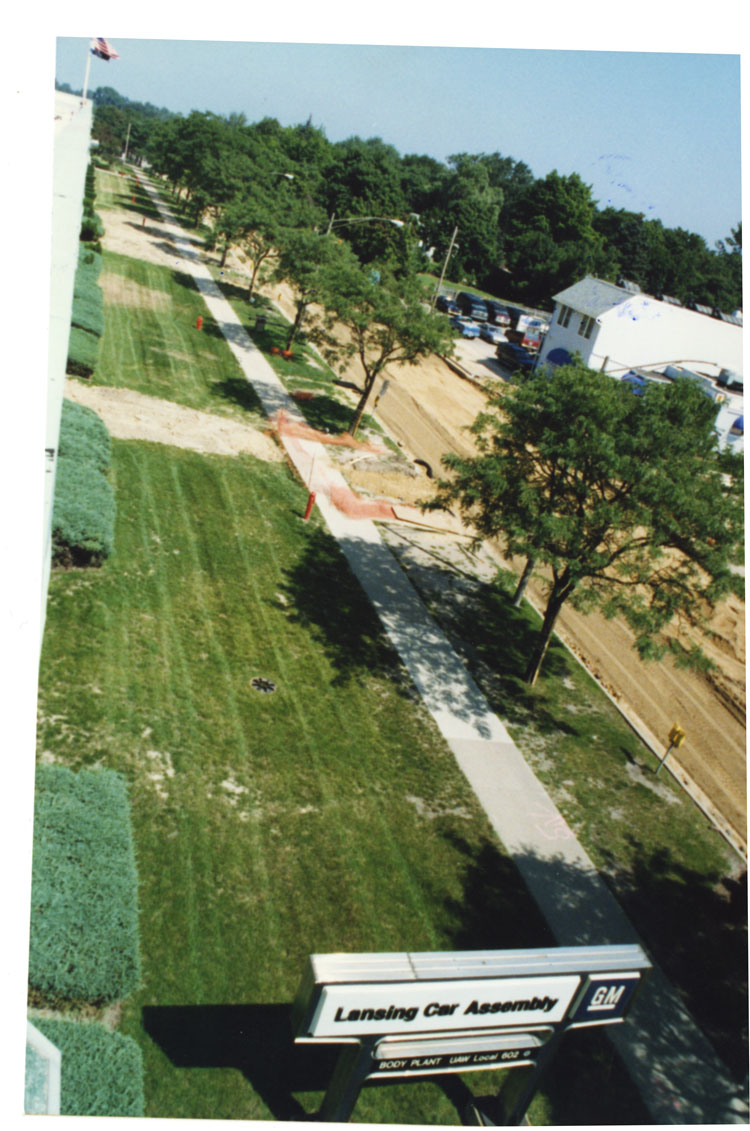 image of Taken from the southeast roof atop Fisher Body building 3X looking north along Verlinden Ave in summer 1998.  The two story white building seen above the trees in the upper right of the photo is Harry's Bar.  The street is gravel as it is being resurfaced.