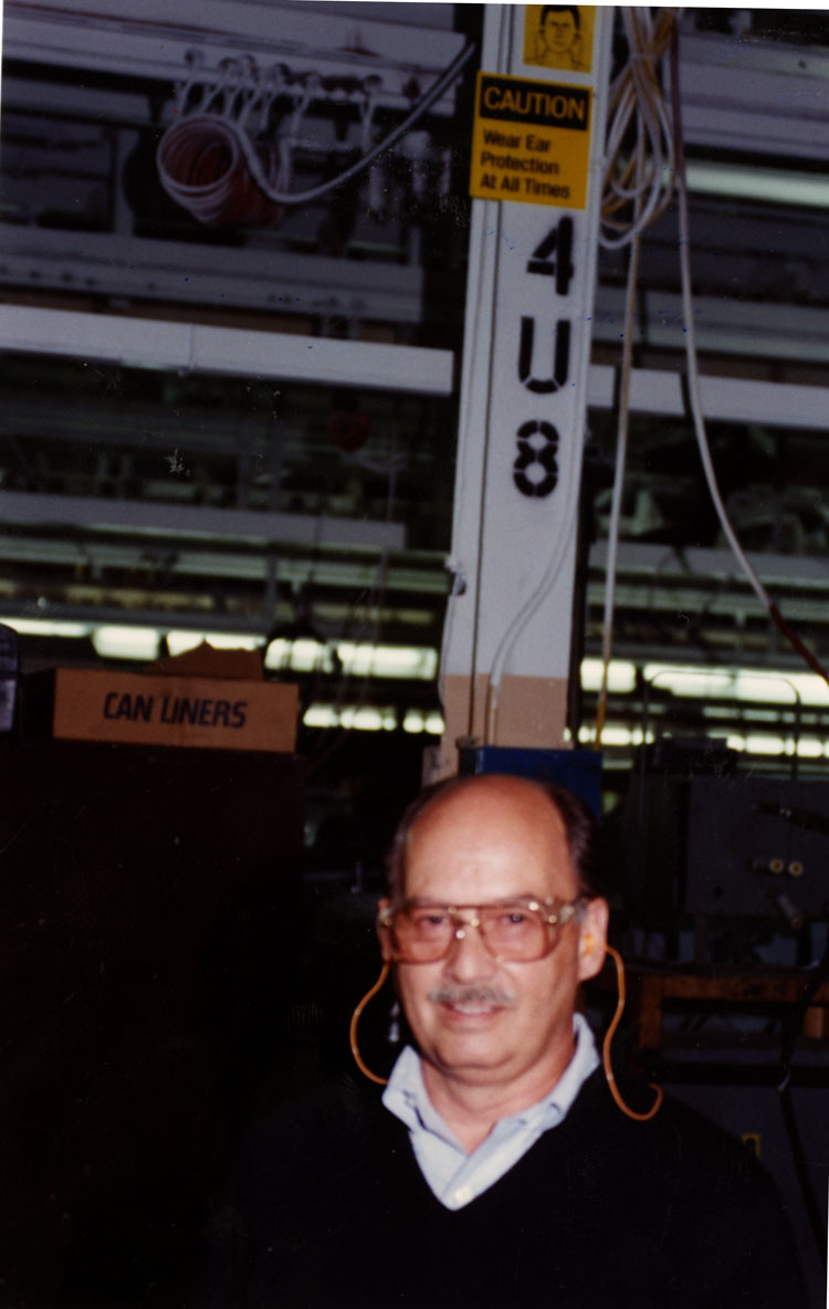 image of Dick Budd demonstrates the correct use of earplugs as the sign mounted at the top of the pillar behind him shows.