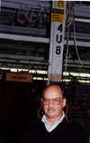 Dick Budd demonstrates the correct use of earplugs as the sign mounted at the top of the pillar behind him shows.