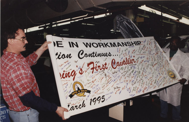 image of Launch of the J-Car (Cavalier and Sunbird) during which the employees signed the banner commemorating the event.  Subjects are, from left to right: Tim Root, Eddies Gentry.