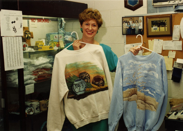 "image of Judy Devers displays merchandise in ""The Emporium"", a gift shop run by salaried women on a volunteer basis raising funds for charity."