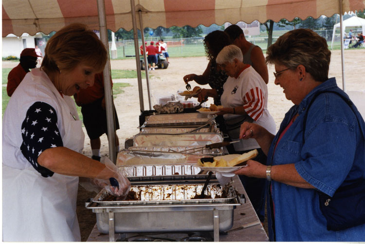 image of Sally Grubaugh serving food at the picnic.