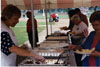 Sally Grubaugh serving food at the picnic.