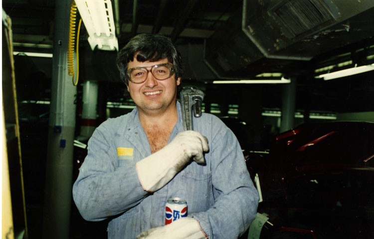 image of Bill Klein carrying a pipe wrench in the Trim Shop inside the Fisher Body Plant.