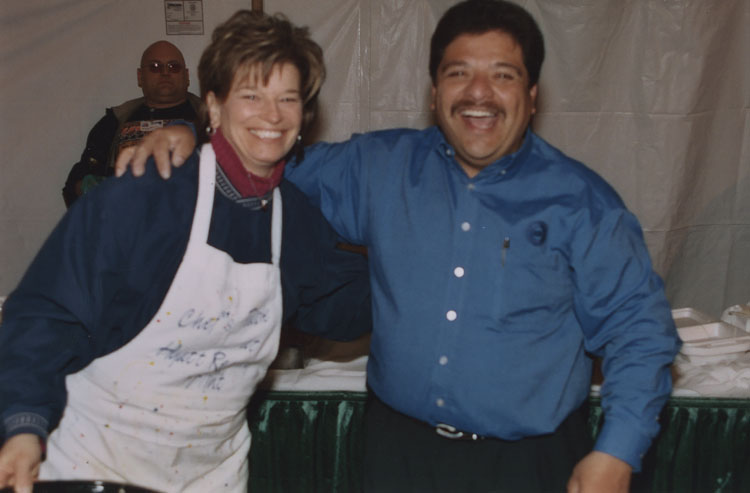 image of Employee appreciation barbeque held in the north parking lot at the Fisher Body Plant shortly before production ceased in 2005.  Subjects are, from left to right: Plant Manager Amy Farmer, Local 602 President Art Luna.  Subject in the background is Richard 'Taz' McDaniel.