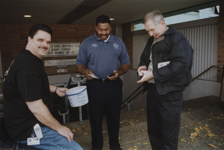 image of George Nelson is conducting a gate collection for an unknown cause and the other two subjects are donating. The persons in the photo are, from left to right: George Nelson, Johny Anthony and Jerry Morse.