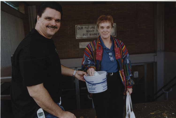 image of George Nelson conducting a gate collection for an unknown cause and the other subject is donating.