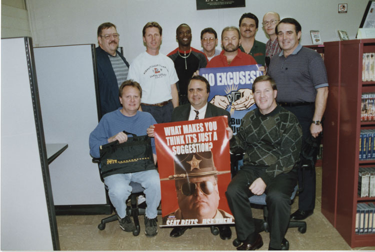 "image of UAW/GM Skill Center at the Fisher Body plant in Lansing, MI.  Plant Safety Advisors promote the use of seat belts in a campaign sponsored by GM and a traffic safety group.  Subjects are: left to right - Front row: Kevin Mix, Unknown, Unknown.  Back row: Paul ""Tiny"" Haynes, Dave Damerow, Tony Bell, Unknown, Robin Boucher (holding poster), George Nelson, Robert Fell, Unknown."