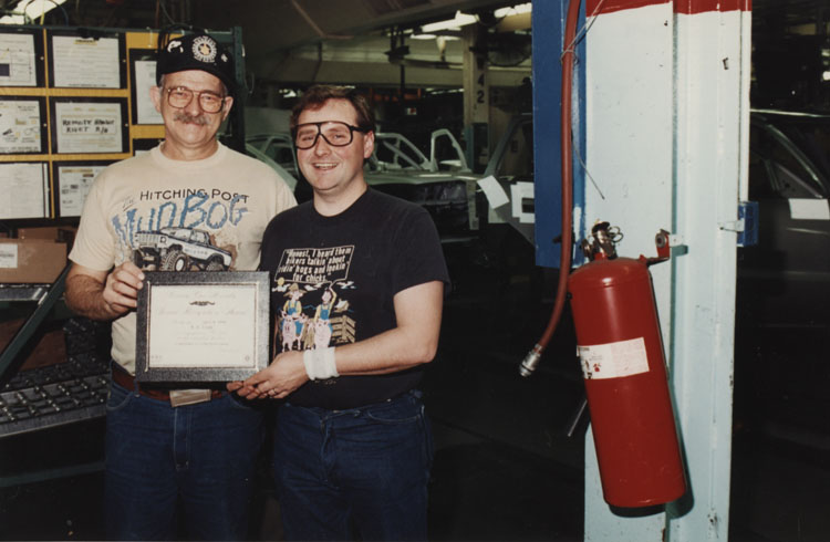 image of Tom Pizzo and Brian Cronk display their Pacesetter Award certificate which they received for extinguishing an incipient stage fire in the executive parking garage.