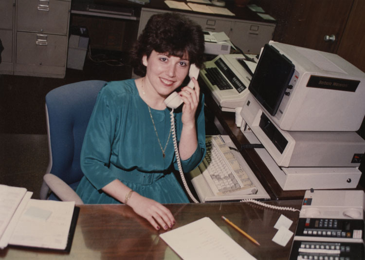 image of Barb Rossi at her desk outside the plant manager's office at Fisher. Given the age of the IBM computer it is likely early 1980s.