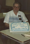 Richard Sanborn shows of the cake at his retirement party.