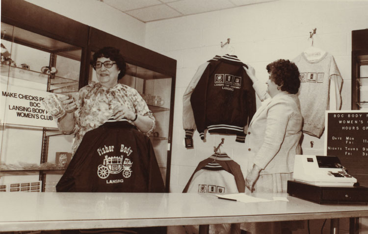 image of Shirley Sanborn displays merchandise at the Women's Club store, The Emporium. Betty White, secretary to the Personnel Director, looks on.