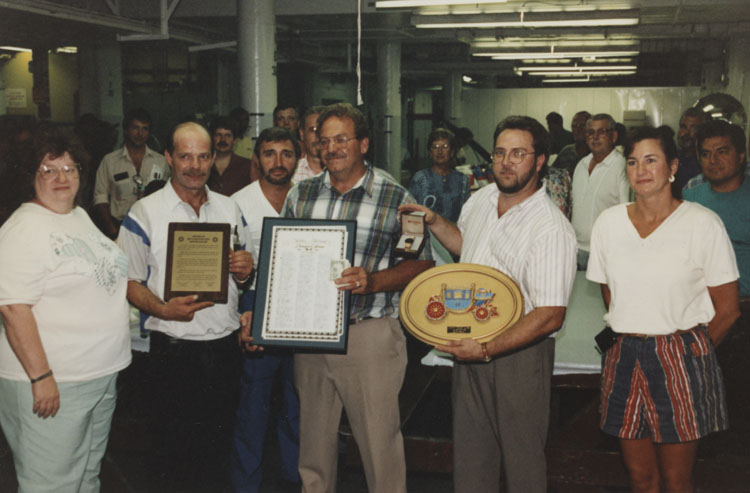 "image of A presentation of certificates, plaques, a watch and a cash donation to Darwin ""Curly"" Jones (UAW Bargaining Committee) on the occasion of his retirement.  Year unknown.  Subjects are, from left to right: Sylvia ""Sam"" Hall (UAW Benefits Rep.), Dan Smith (UAW Bargaining Committee), Bob Bobzien, Darwyn ""Curly"" Jones (UAW Bargaining Committee), Gayle Gooslin (Local 602 Book Keeper), Garry Bernath (Local 602 President), Russ Bower (UAW Safety Representative), Renida (RT) Taylor (UAW Bargaining Committee), Unknown."