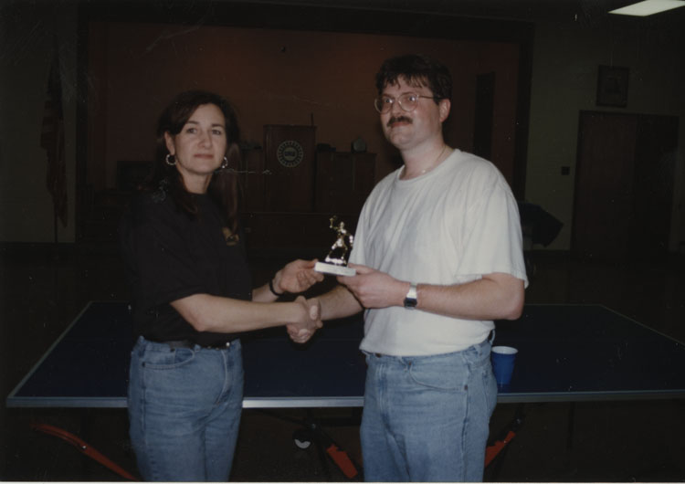 image of Renida (RT) Taylor giving a trophy to a ping-pong champion following an event conducted by the Recreation Committee.