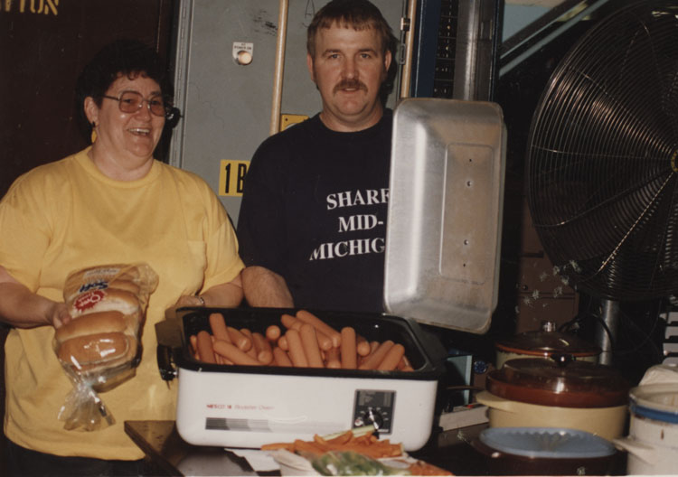 image of Diana Valenta and Bruce McConnell prepare food for what is either a department potluck or a fund raiser.