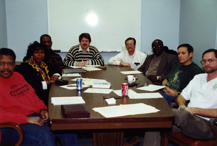image of Meeting of the UAW Chaplain Committee. Subjects are, from left to right: Unknown, Martha Adams, Unknown, David Brown, Doug Gross, Kirklin Hall, Walt Saxton, Keith Hartman; all UAW members and several are ordained ministers.