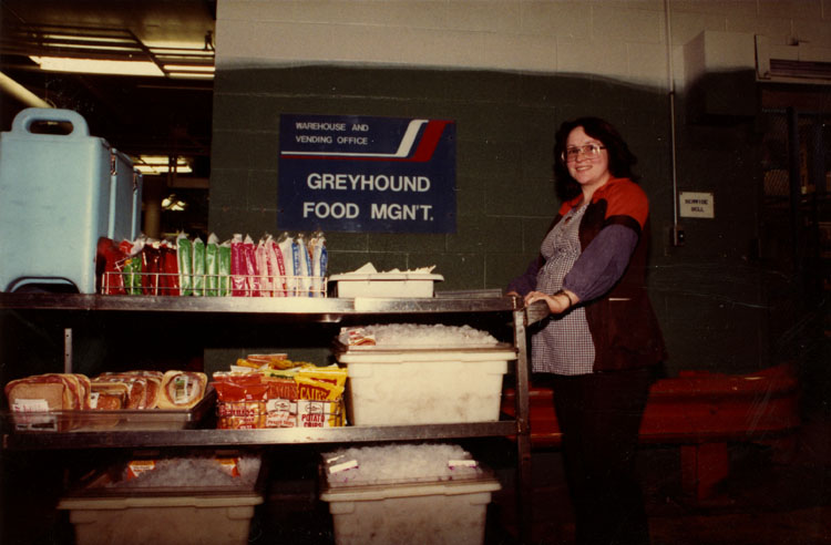 "image of Behind the cafeteria kitchen in the Fisher Body Plant in Lansing, MI.  Year unknown but before the fall of 1984.  Subject is Tammi Nickerson, an employee of Greyhound Food Management, preparing to take the ""Wagon"", a snack cart of food, candy, and beverages, down to the factory floor.  The Wagon was a negotiated feature of many GM plants.  In addition to twice-daily hygiene and coffee breaks, a six-minute Wagon break was included both before and after the lunch period.  Lansing Fisher Body was the last GM facility have Wagon breaks.  The Wagon breaks were renewed in each set of local negotiations until it was eliminated as part of the 1984 local negotiations."