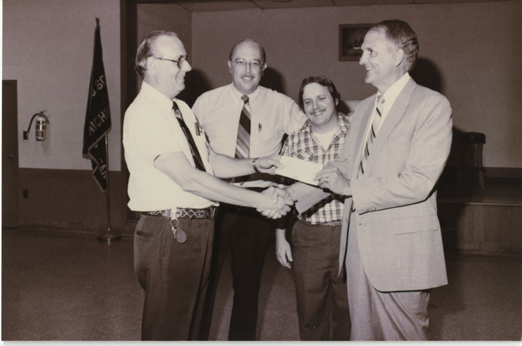image of Fisher Body Plant Manager Frank Shotters (on the right) receives a contributon check for a charity event. Subjects are, from left to right: Unknown (possibly Lloyd Cain – former Local 602 President), John Rosendahl, Mike Clark, Frank Shotters (Plant Manager).