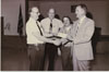 Fisher Body Plant Manager Frank Shotters (on the right) receives a contributon check for a charity event. Subjects are, from left to right: Unknown (possibly Lloyd Cain – former Local 602 President), John Rosendahl, Mike Clark, Frank Shotters (Plant Manager).