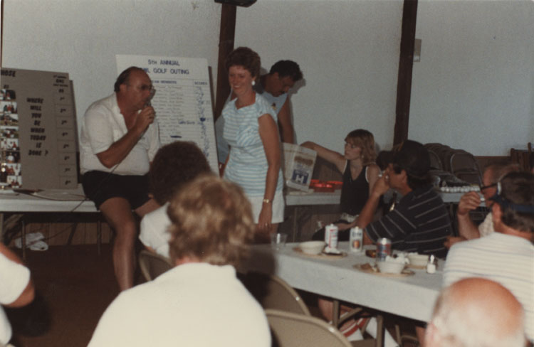 image of Award ceremony following the 5th Annual QWL (Quality of Work Life) Golf Outing.  Year unknown.  Subject seated on the table is John Rosendahl.  Woman standing is Judy Devers.  Other subjects unknown.  QWL began in the early 1980s.  It was an attempt by GM and the UAW to empower employees, improve communication, and improve morale.  Several activities like this golf outing were conducted under the umbrella of QWL.