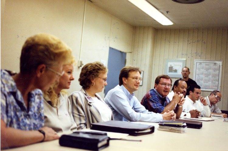image of Management negotiation team gathers in a conference room likely during the 1999 local contract negotiations. Subjects are, from left to right: Connie Jaquette (Trim Manager), Mary Watson (Labor Relations), Karen Feazel (Labor Relations), Michael Reinerth (Labor Relations), Jim Gaunt (Personnel Director), John Couthen (Labor Relations), Unknown, Ralph Koren (Labor Relations).  Subject standing in the background is Matt Strickling (UAW Local 602 President).