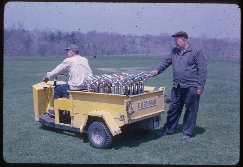 Joe Butler beside Cushman Sprinkler Transport
